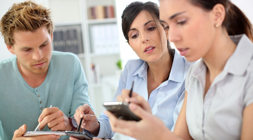 Young people using smartphones in office